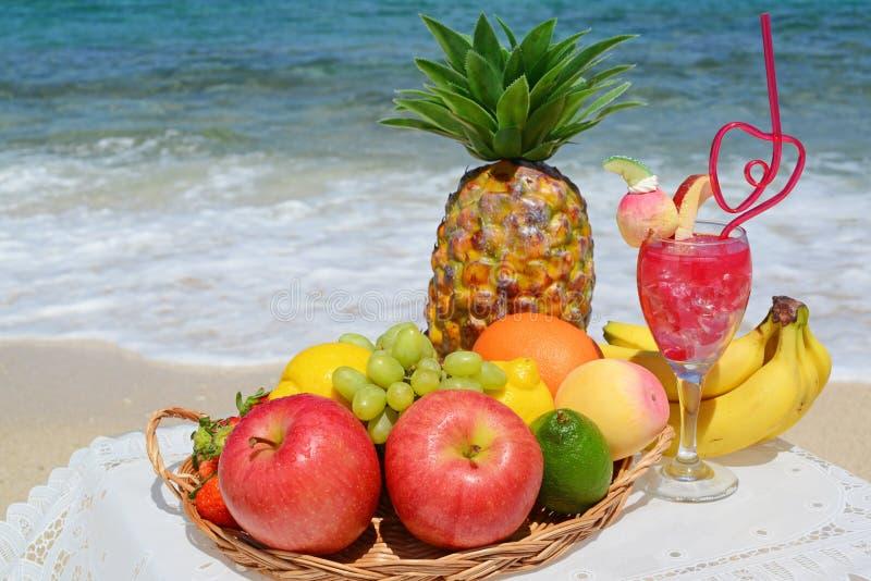 Tropische vruchten en drank op het strand stock foto