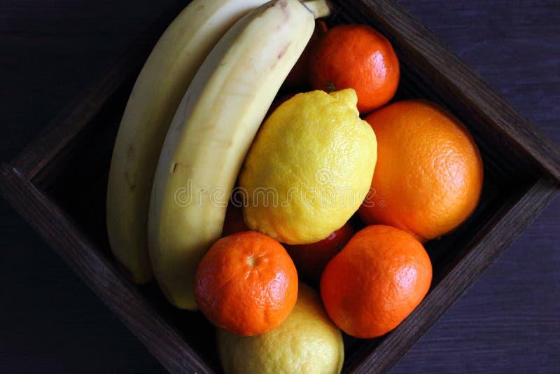 Tropische vruchten in houten mand op de mening van de lijstbovenkant Sappige mandarins, sinaasappel, citroen en banaan Zoete vita stock fotografie