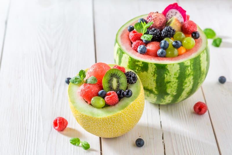 Tropische vruchten salade in meloen en watermeloen in zonnige keuken stock fotografie