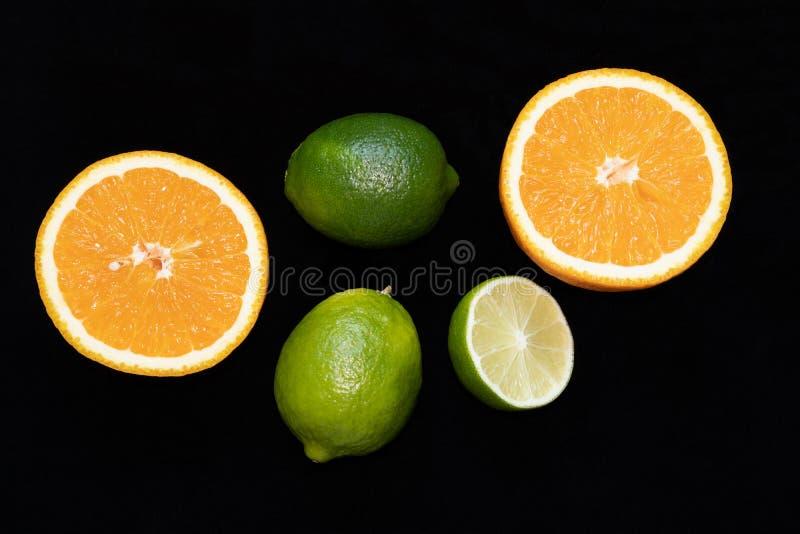 Tropische vruchten sinaasappel en kalk in gehele vorm en gesneden op zwarte achtergrond royalty-vrije stock afbeelding