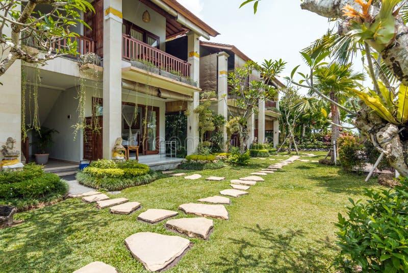Tropischer grüner Gartenbereich am traditionellen Landhaus lizenzfreies stockfoto