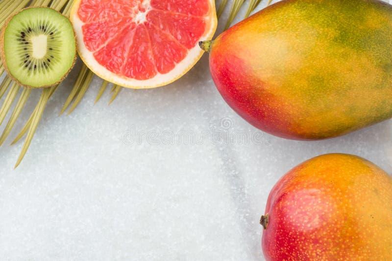 Tropischer Natur-Hintergrund-reife saftige rote Mango-Scheiben von Pampelmusen-Kiwi Spiky Green Yellowish Palm-Blatt Gesunder Nah lizenzfreies stockfoto