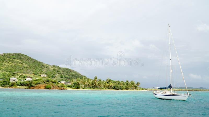 Tropischer Ozean und Strand mit Segelbootsyacht in den Tobago-Cays, St. Vincent und die Grenadinen, Karibisches Meer lizenzfreie stockbilder