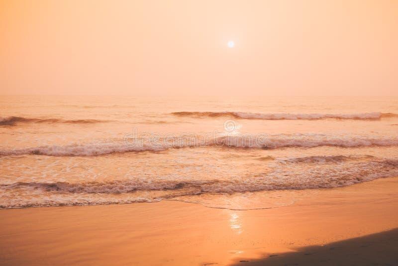 Tropischer sandiger Strand, Seeansicht während eines bunten Sonnenuntergangs stockbild