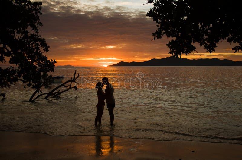 Tropischer Sonnenuntergang, Ozeanufer mit Schattenbild eines Liebhaberpaares lizenzfreies stockfoto