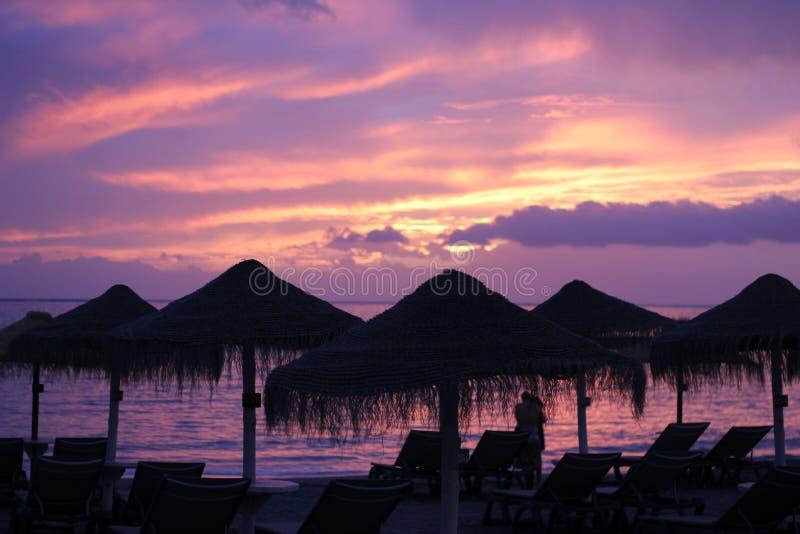 Tropischer Sonnenuntergang und ein Paar stockbild