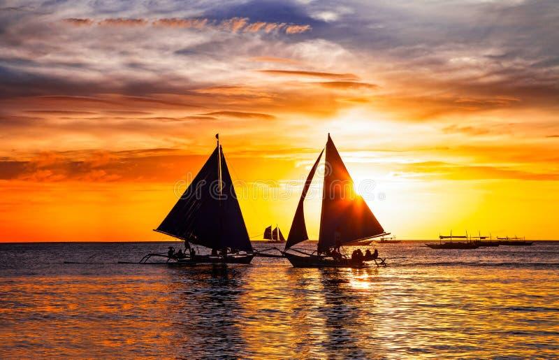 Tropischer Sonnenuntergang und Schattenbild von Segelbooten in Boracay-Insel lizenzfreie stockfotos