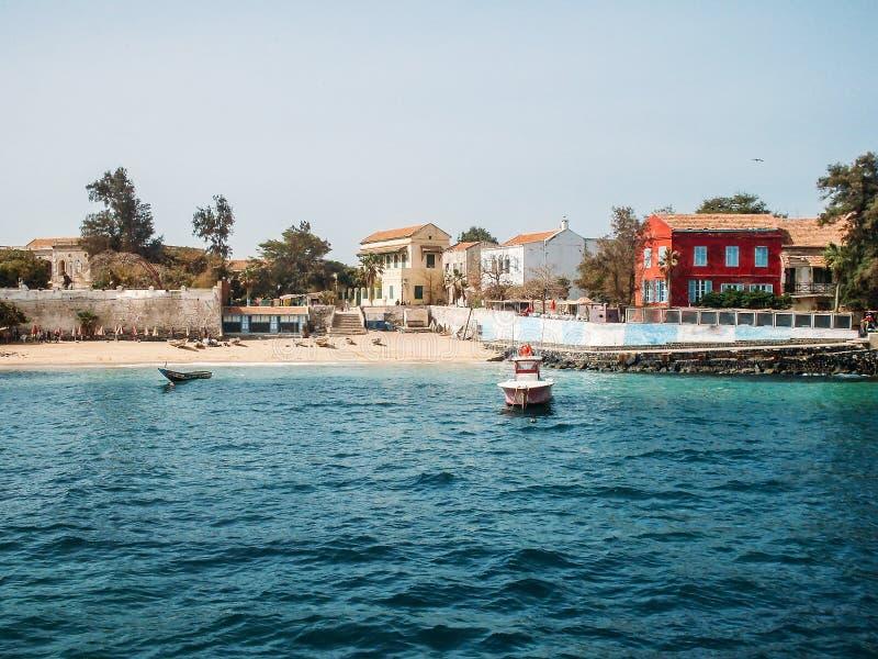 Tropischer Strand durch Meer mit Häusern und Booten, Ansicht vom Wasser, Paradiesferien stockfotografie