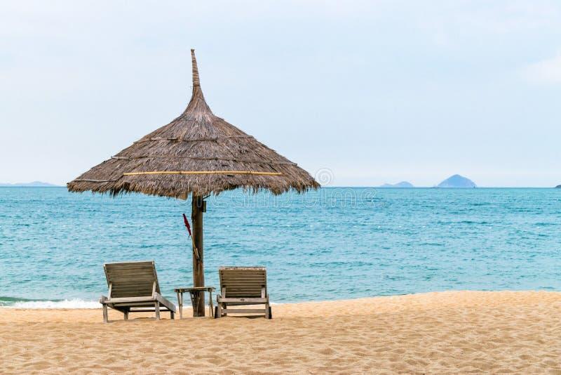 Tropischer Strand mit H?tte und St?hle nahe Ozean lizenzfreies stockfoto