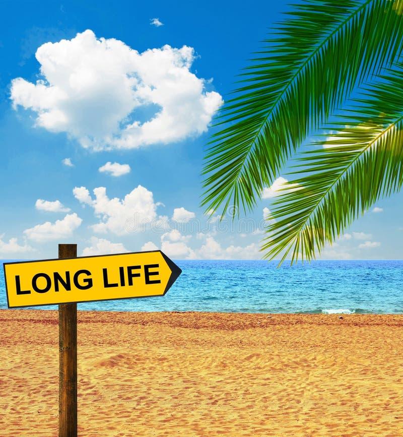 Tropischer Strand und Richtungstafel, die LANGES LEBEN sagt stockfotos