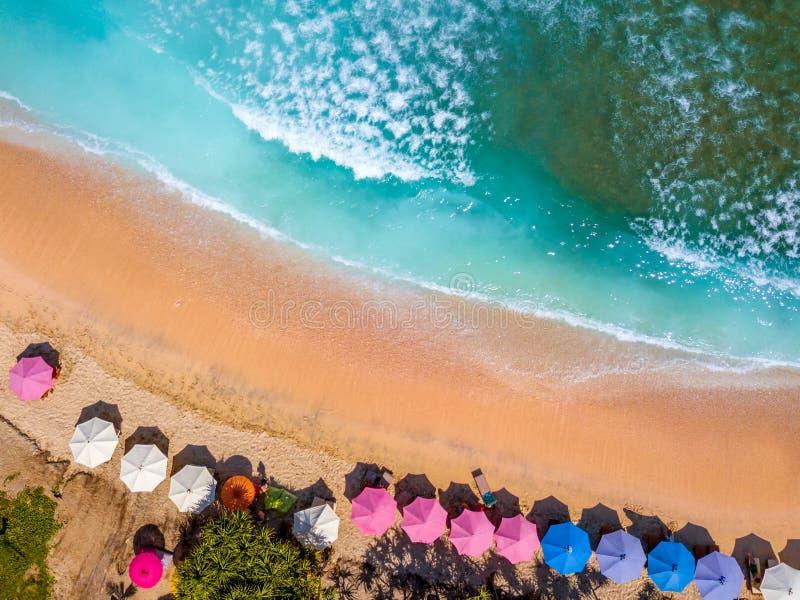 Tropischer Strand und Sonnenschirme Schattenbild des kauernden Geschäftsmannes lizenzfreies stockbild