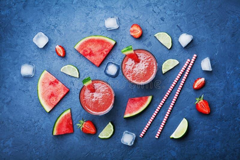 Tropischer Wassermelone Smoothie mit Scheiben der Frucht auf blauer Tischplatteansicht in Ebene legen Art Sommer Detoxsaft stockfotos
