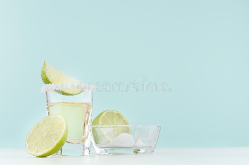Tropisches Alkoholschussgetr?nk - Tequila mit salziger Kante, Scheibenkalk auf elegantem gr?ne Farbhintergrund und wei?es h?lzern stockfotografie