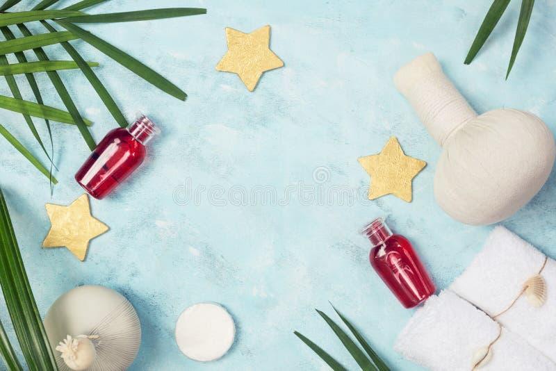 Tropisches Badekurortmodell: weiße Tücher, rote Shampooflaschen, thailändisches masage bauscht sich, goldene Sterne und grüner Fa stockfotos