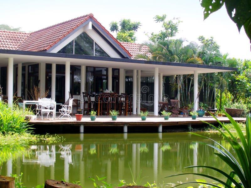 Tropisches Haus u. natürlicher Teich stockfoto