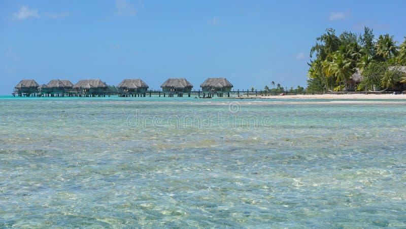 Tropisk ö med bungalower över vatten fotografering för bildbyråer