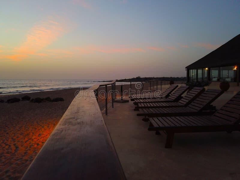 Tropisk bakgrund med par av solstolar på solnedgången vid havet Det är den härliga sikten av den guld- solen från hotell royaltyfri bild