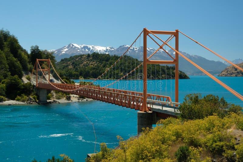 Tropisk blå sjögeneral Carrera, Chile med den orange bron royaltyfri fotografi