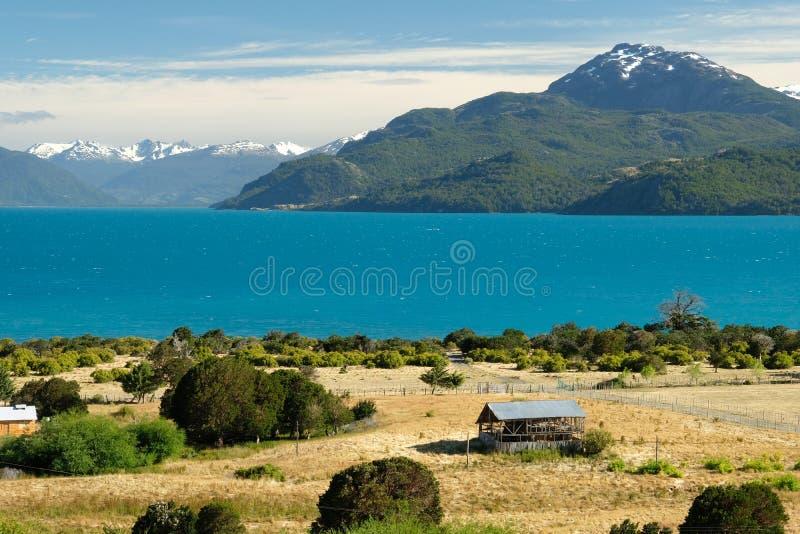 Tropisk blå sjögeneral Carrera, Chile med landskapberg och ladugården arkivbild