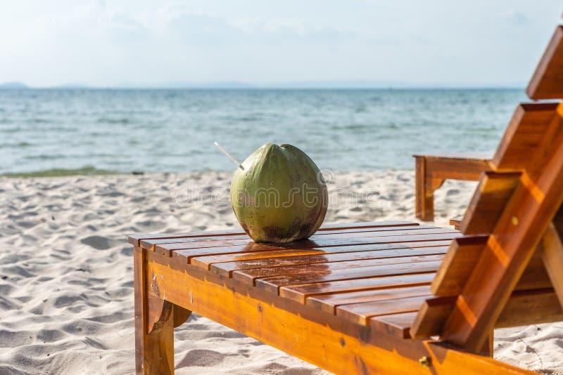 Tropisk drink för kokosnöt på stol på den vita sandstranden royaltyfria foton