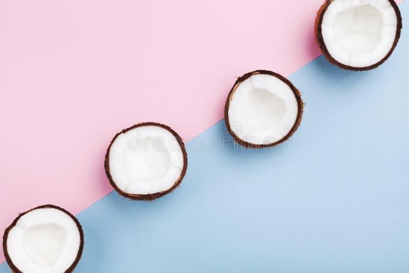 Tropisk frukt för kokosnöt som är halv på bästa sikt för minsta pastellfärgad bakgrund Idérik sommarmodell för modern design Lekm royaltyfri foto