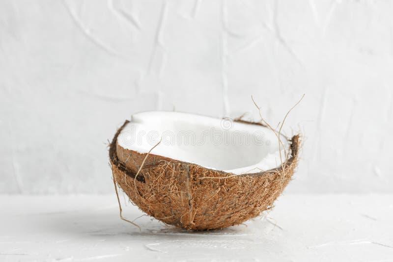 Tropisk kokosnöt för halva på trätabellen mot vit bakgrund royaltyfria bilder