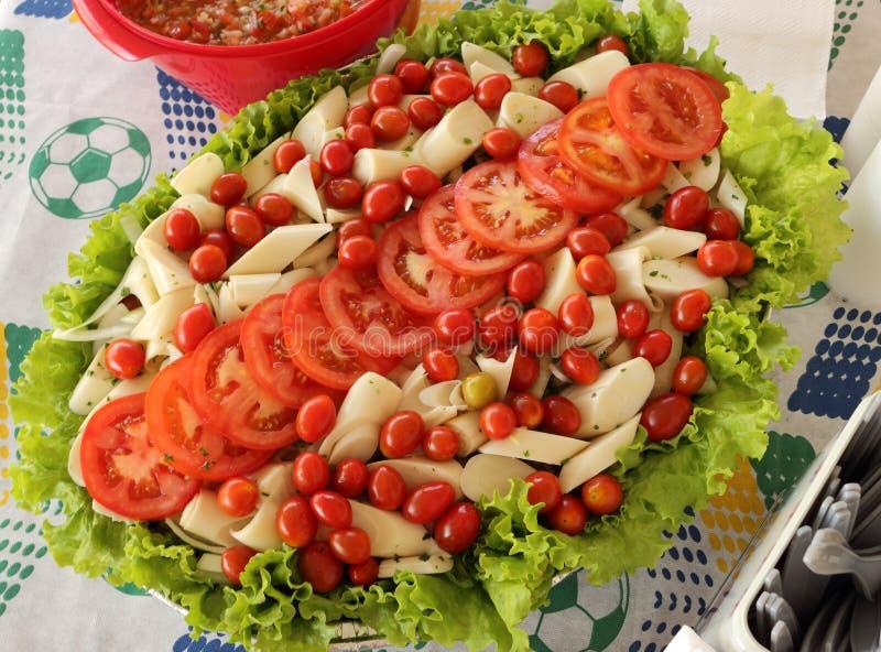 Tropisk sallad med tomater, grönsallat, körsbärsröda tomater, gömma i handflatan hjärta Att att vara sunt arkivfoto