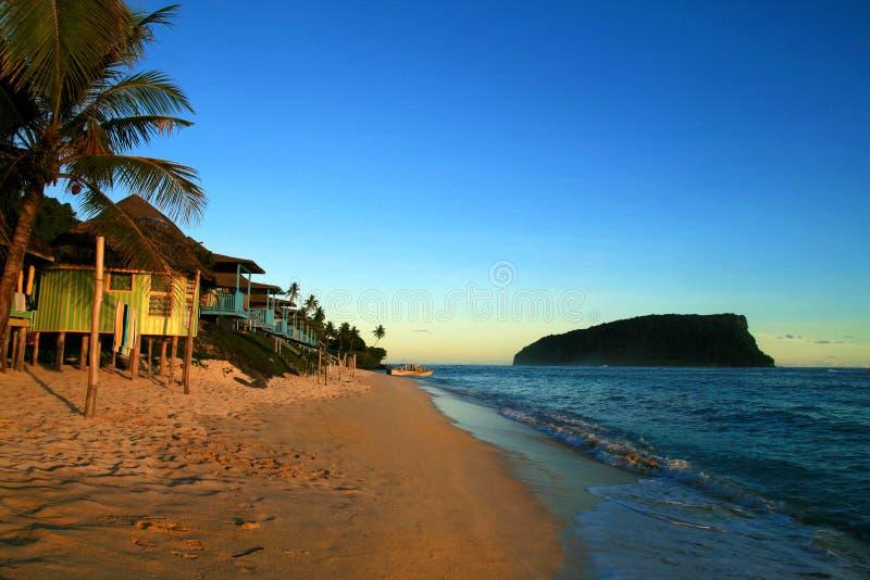 Tropisk sandig strand för Stillahavs- ö med traditionella strandfales efter solnedgångskymning, Lalomanu strand Samoa, Upolu, Sti royaltyfria foton