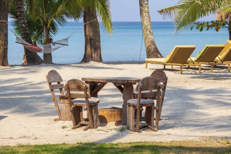 Tropisk sandstrand med trätabellen och stolar, chaisevardagsrum, hängmatta och palmträd mot bakgrunden av det blåa havet, arkivbild