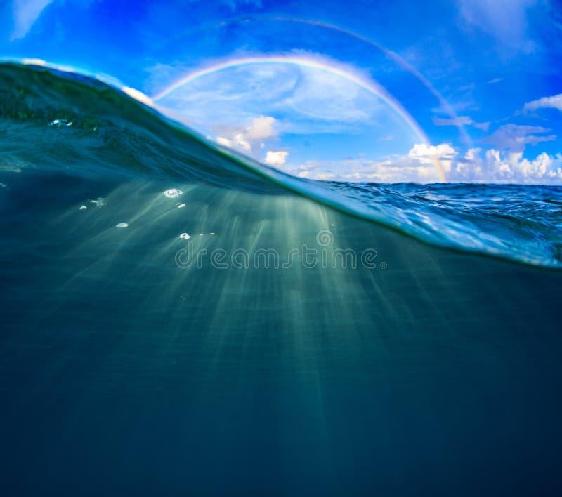 Tropisk Seascape för halvt vatten med regnbågen royaltyfri bild
