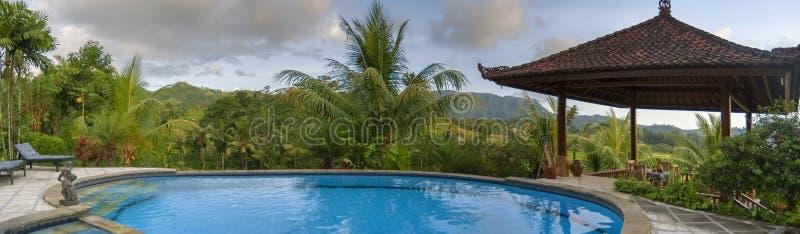 Tropisk semesterortsimbassäng på ön av Bali på solnedgången arkivbild