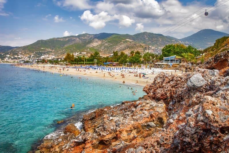 Tropisk semesterortstrand för paradis i Alanya, Turkiet Hav och steniga berg på den turkiska stranden på solig dag för sommar med arkivfoton