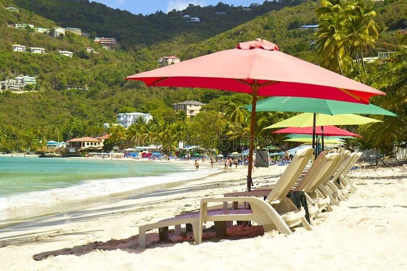 Tropisk strand med paraplyer, Cane Garden Bay, Tortola som är karibisk arkivfoto