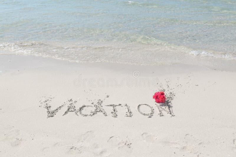 Tropisk strand och hav med meddelandet som är skriftligt på sanden royaltyfri fotografi