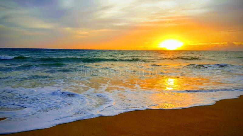 Tropisk strandsolnedgång med vågen i havet på den Maichao stranden i den Phuket staden, Thailand royaltyfri foto