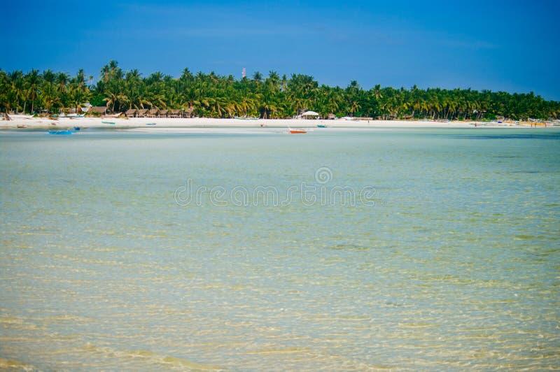 Tropisk vit sandstrand med gröna palmträd och parkerade fiskebåtar i sanden Exotiskt öparadis arkivbilder