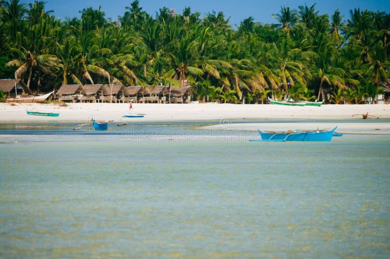 Tropisk vit sandstrand med gröna palmträd och parkerade fiskebåtar i sanden Exotiskt öparadis arkivbild