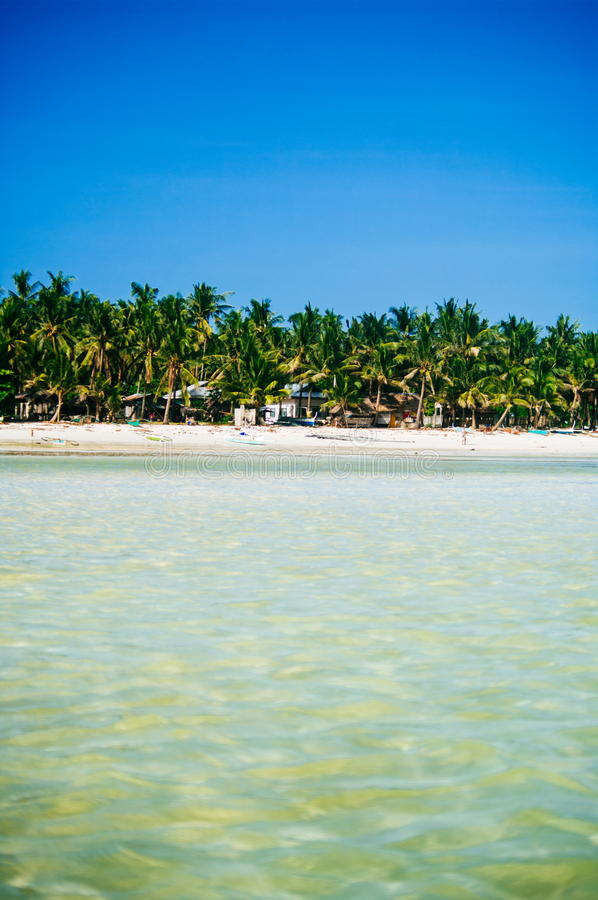 Tropisk vit sandstrand med gröna palmträd och parkerade fiskebåtar i sanden Exotiskt öparadis arkivfoto