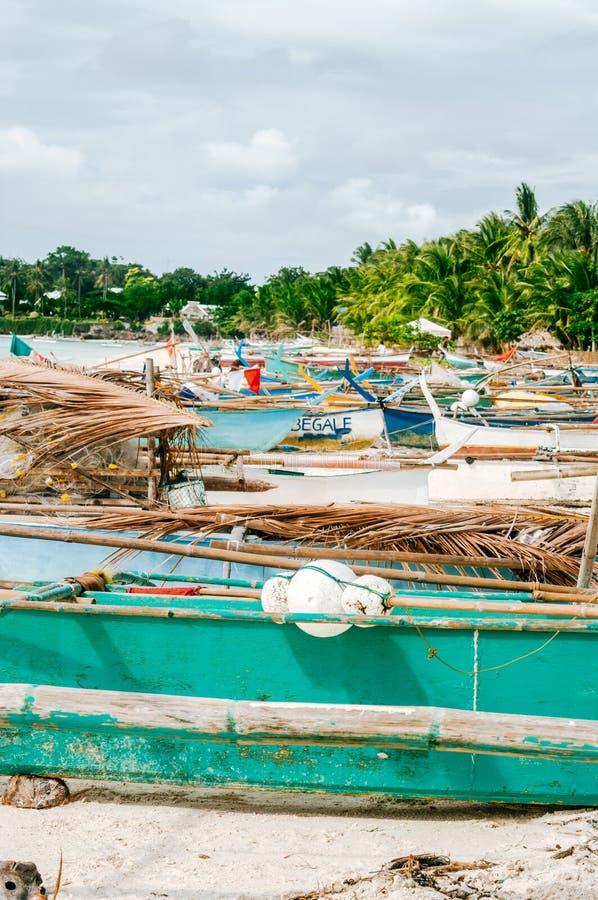 Tropisk vit sandstrand med gröna palmträd och parkerade fiskebåtar i sanden Exotiskt öparadis royaltyfri bild
