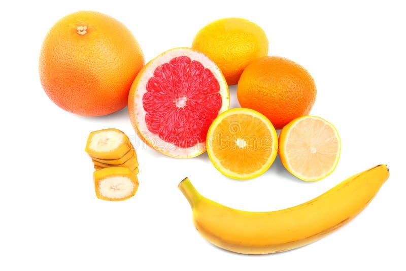 Tropiska bananer för helhet och för snitt och saftiga sura citroner och mogna ljusa apelsiner för grapefrukter som och isoleras p arkivbild