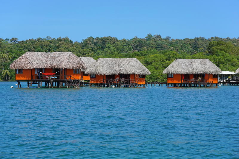 Tropiska bungalower över vatten arkivbilder