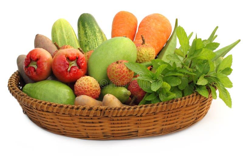 Tropiska frukter och grönsaker på en korg arkivbild