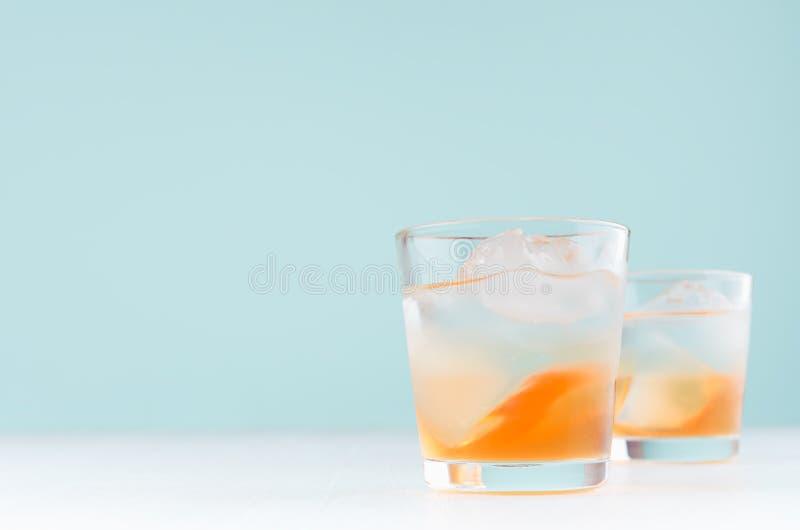 Tropiska kalla randiga alkoholapelsiner dricker med orange starksprit, iskuber, vodka p? elegant bakgrund f?r gr?n f?rg royaltyfri foto