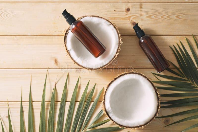 Tropiskt blad, omsorgskönhetsmedel och kokosnöt på en trätabell Top beskådar Hjälpmedel för hår, kropp, hud flatlay fotografering för bildbyråer