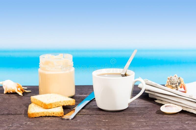 Tropiskt hav som ses fr?n fartyget Kr?m, kaffe och tidning p? tabellen Frukost i semester royaltyfri bild