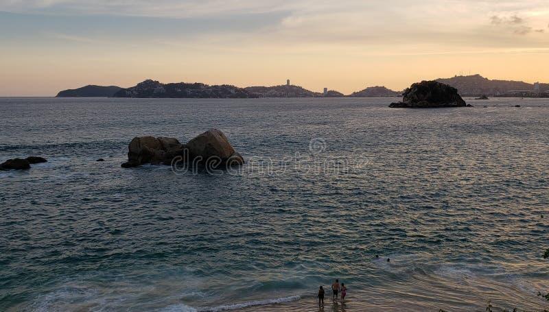 Tropiskt landskap i den huvudsakliga fjärden av Acapulco, Mexico under solnedgång arkivfoto