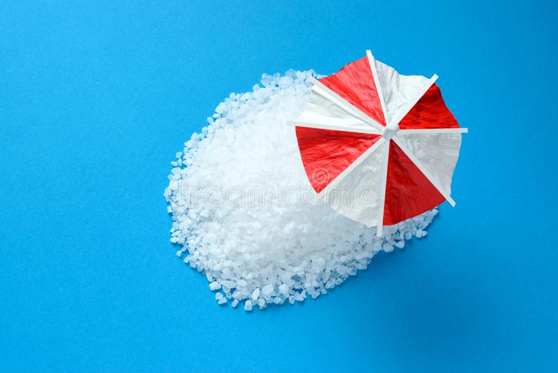 Tropiskt strandbegrepp som göras av salt vit och solparaplyet arkivbild