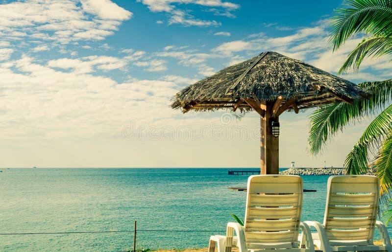 Tropiskt strandlandskap med den strandstolar och slags solskydd på sand n royaltyfria bilder