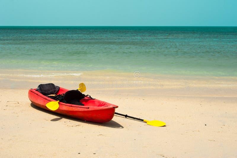 Tropiskt strandlandskap med det röda kanotfartyget royaltyfria foton