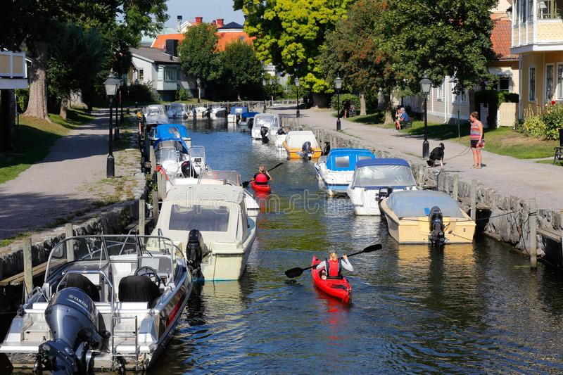 Trosa river. Trosa, Sweden - August 28, 2019: Two red sea kayaks in the Trosa river with moored pleasure boats stock images
